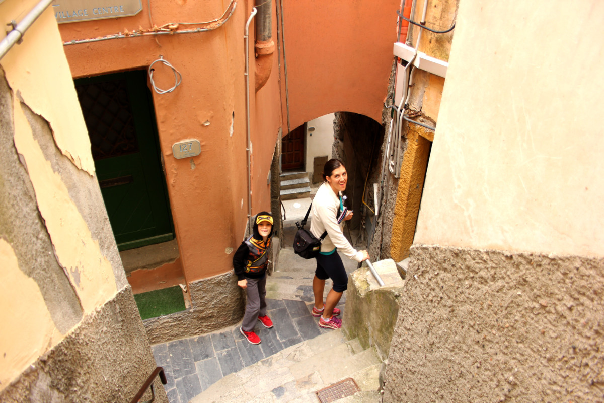 A mom and son walk in a narrow passage way in Riomaggiore, Cinque Terre Italy