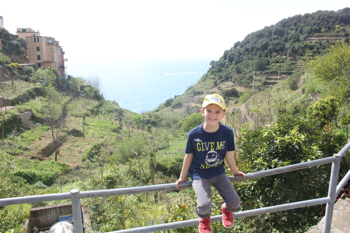 A young boy hikes between Vernazza and Coniglia in Cinque Terre, Italy