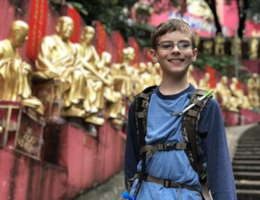 Young Boy stands on a path with golden buddha statues in the background