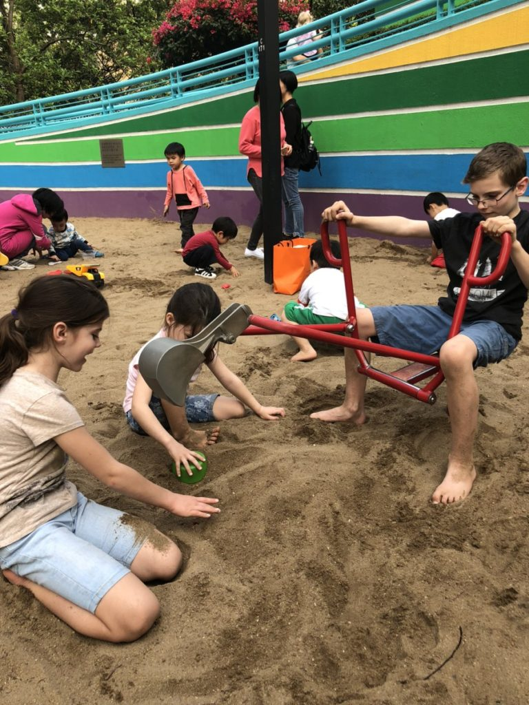 Children play at Hong Kong Park Sancbox with a digger in a sandbox