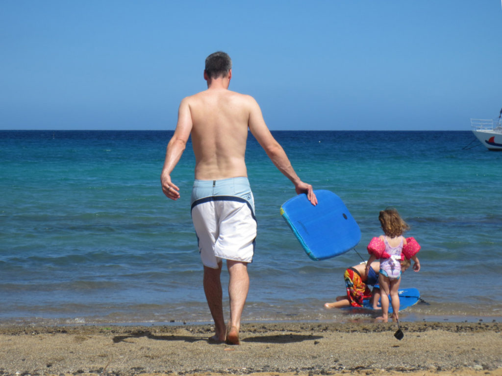 Father and daughter head to the ocean with a boogie board ath A-Bay on the Big Island in Hawaii