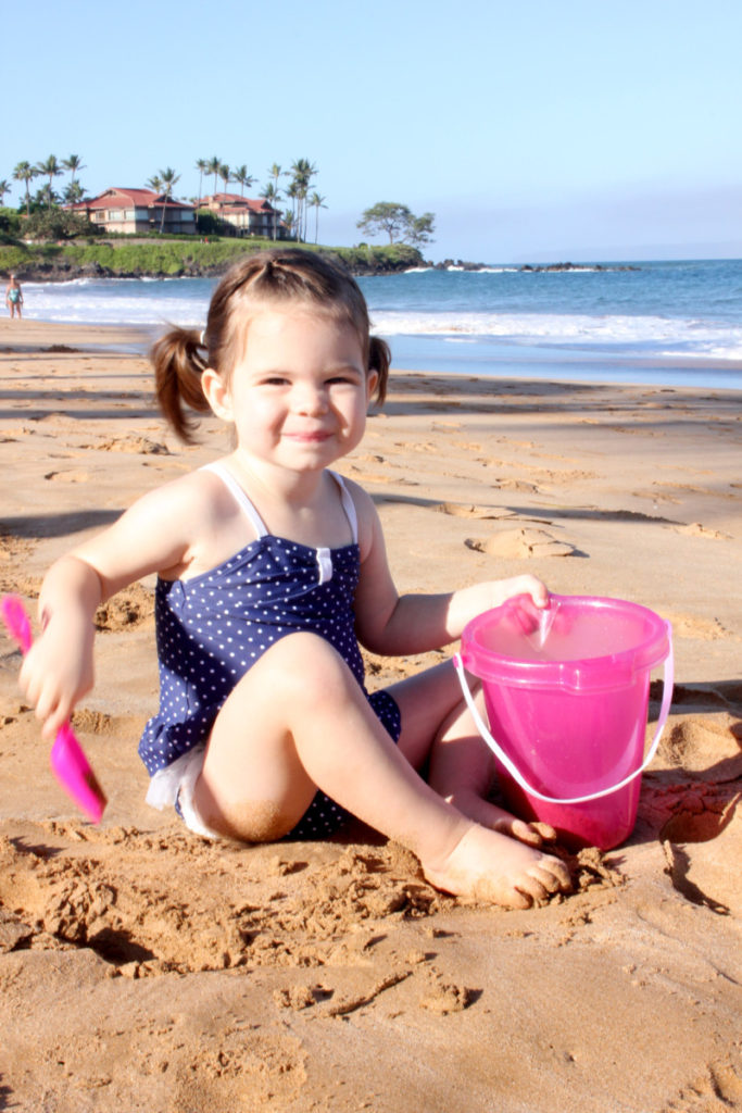Young girl digs in the sand at Ka'anapali beach on Maui in Hawaii