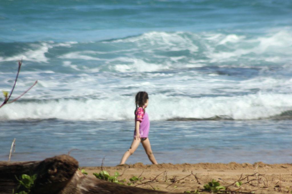 Girl Plays in the ocean at Tunnels Beach on Kauai, Hawaii