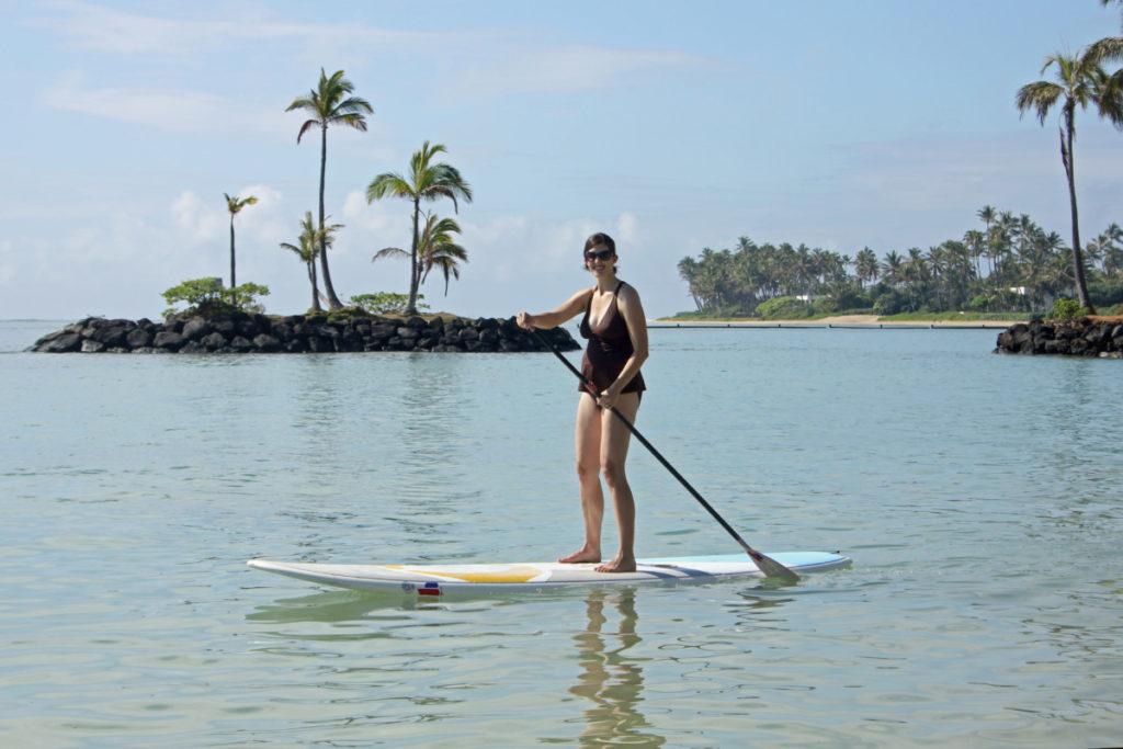 woman paddleboarding on a bay in Oahu, Hawaii