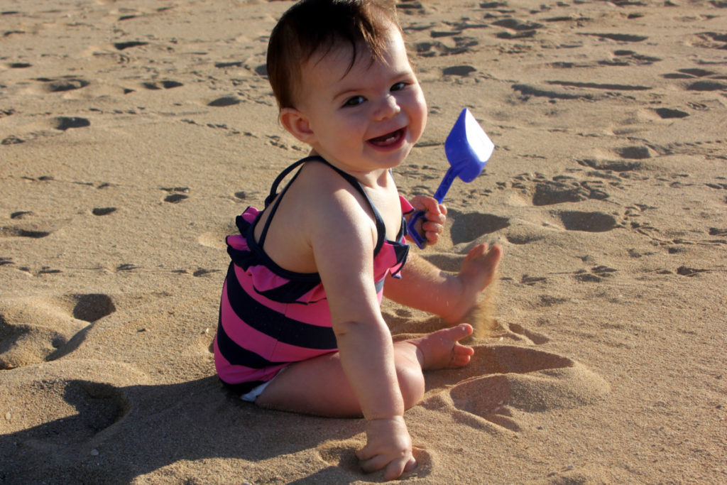 baby plays in the sand at Ko'olina beach on Oahu, Hawaii