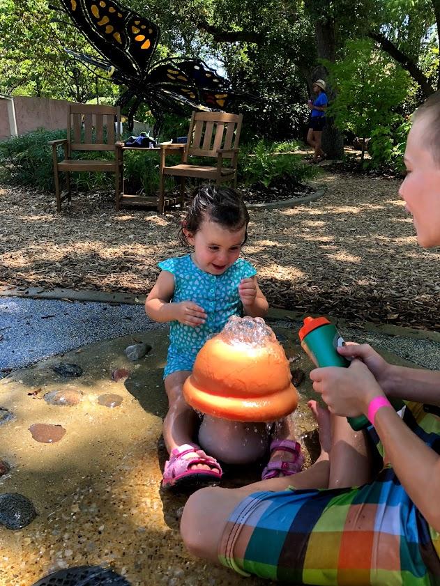 a girl plays in water mushroom at Dallas Arboretum