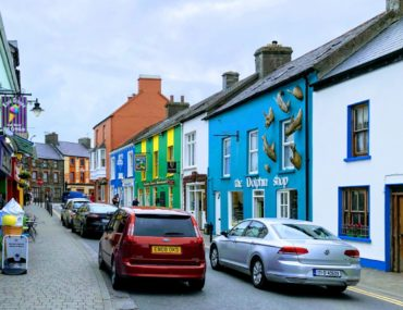 A small car driving in Ireland through a narrow road with parked cars in Dingle