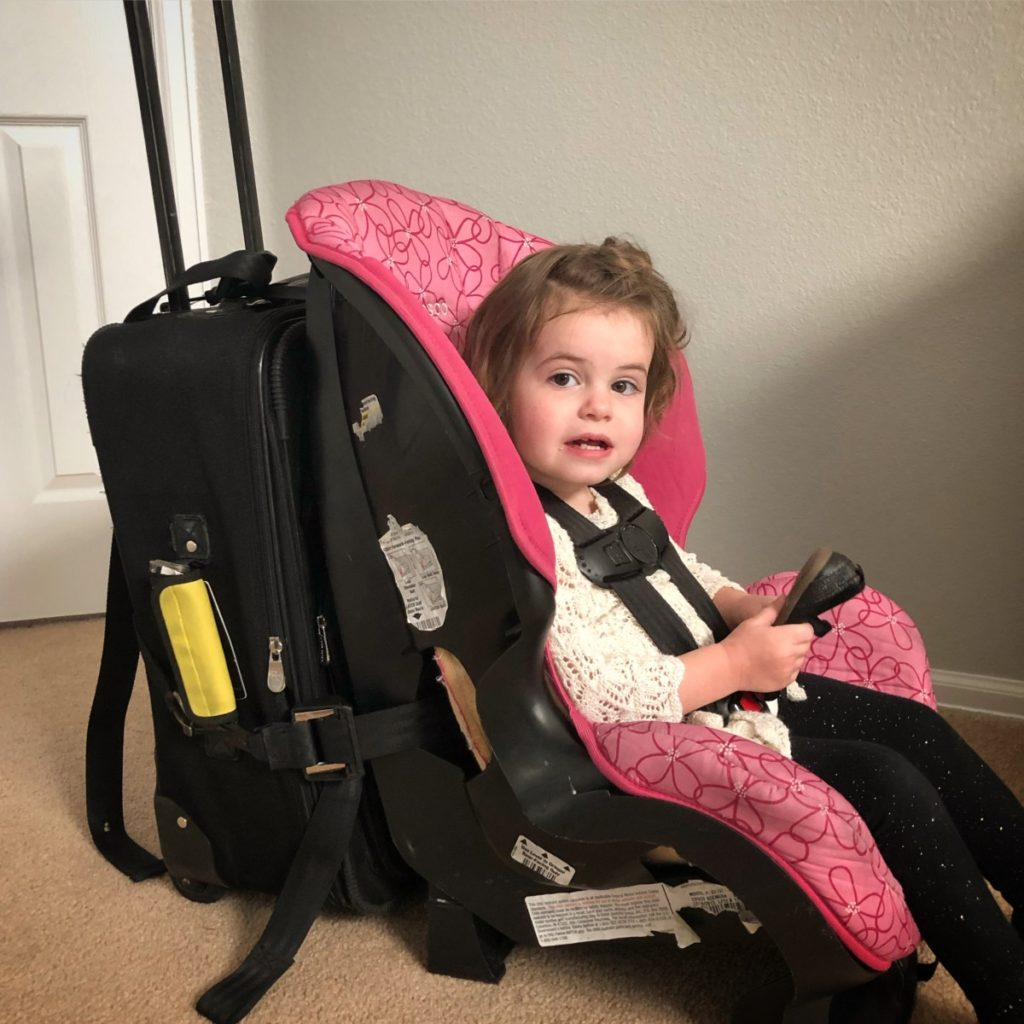 Toddler in a car seat attached to a carry-on