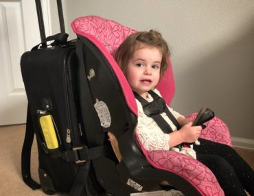 Baby strapped into a car seat is attached to luggage for travels