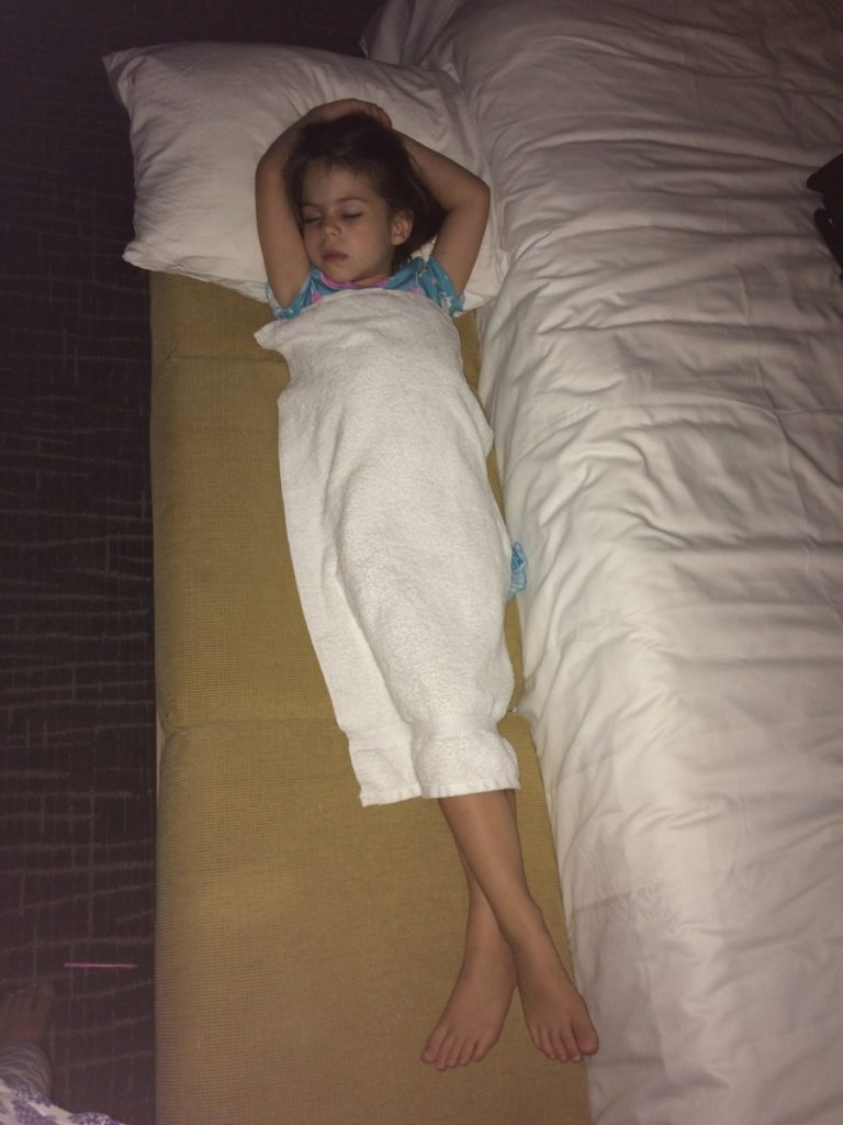 Young Girl sleeping in a hotel room with a towel for a blanket