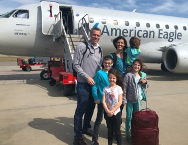 a Family of 6 stands on the tarmac in front of a small American Airlines Airplane