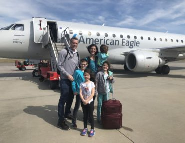 Family of 6 stand on the tarmac in front of an American Eagle plane