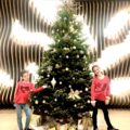 2 girls stand in front of the Christmas tree having family fun at the Westin DFW airport