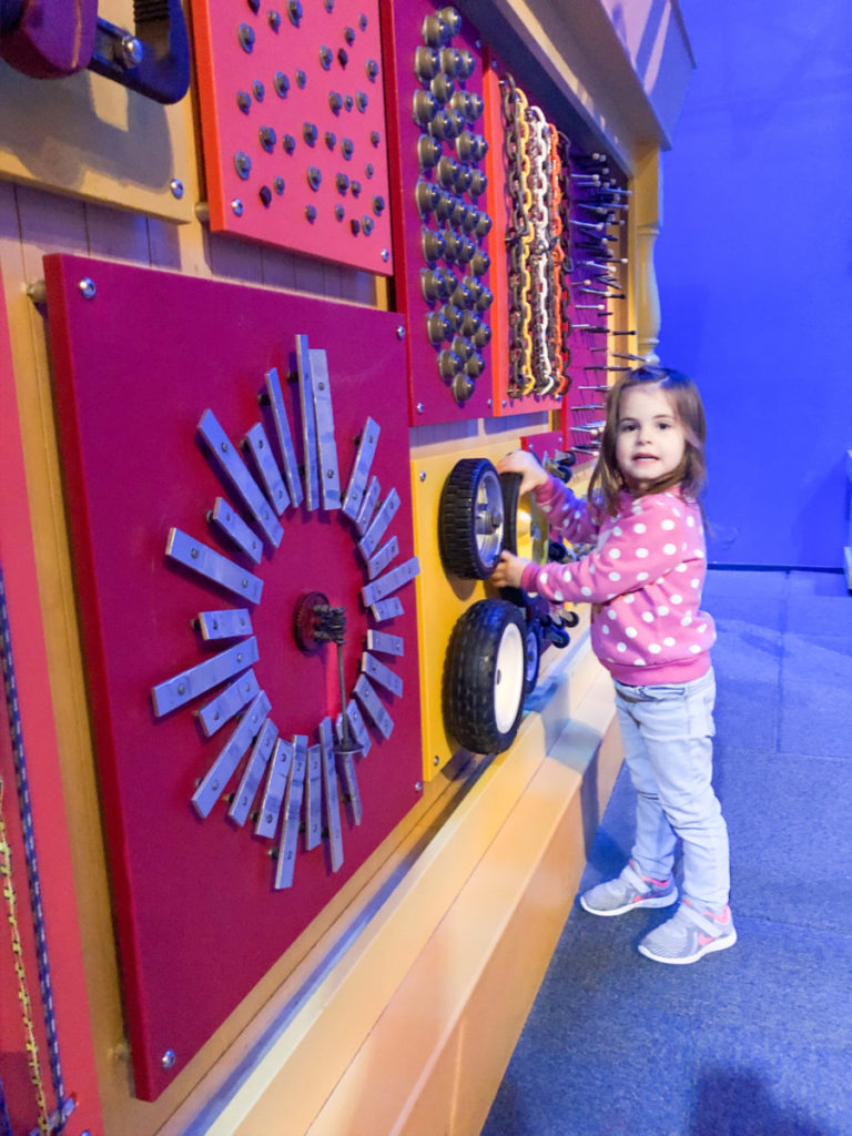 A toddler touches a wall of gadgets at the Oklahoma Science Museum at OKC with kids