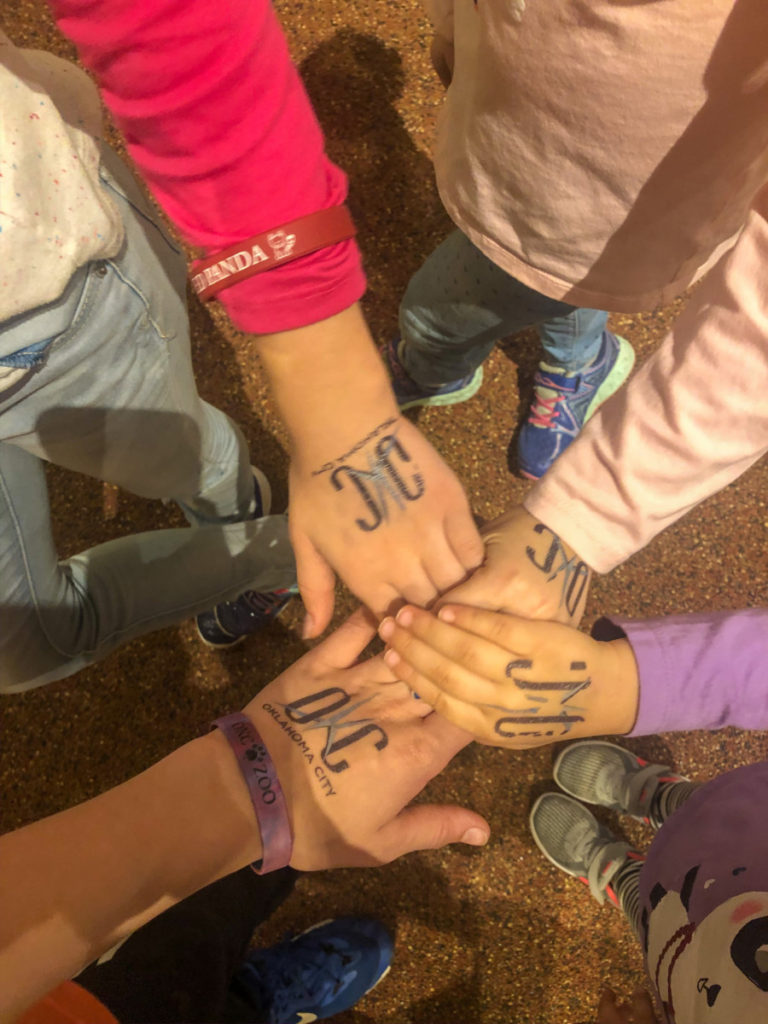 4 kids hands with OKC oklahoma City Tattoos