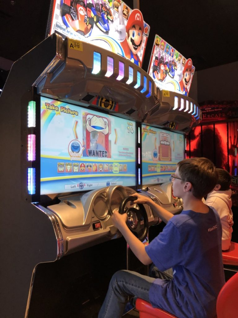 A boy plays mario cart at HeyDay arcades in OKC bricktown district