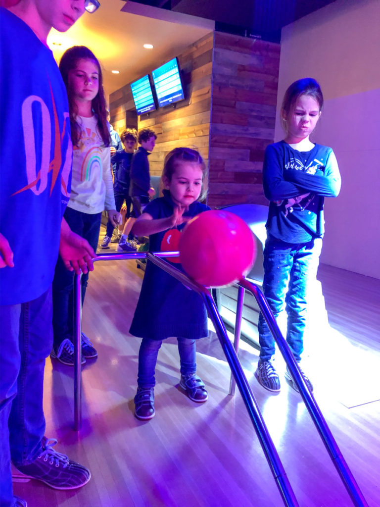 Toddler bowls while siblings look mad at the bowling alley in Oklahoma City, OKC with kids
