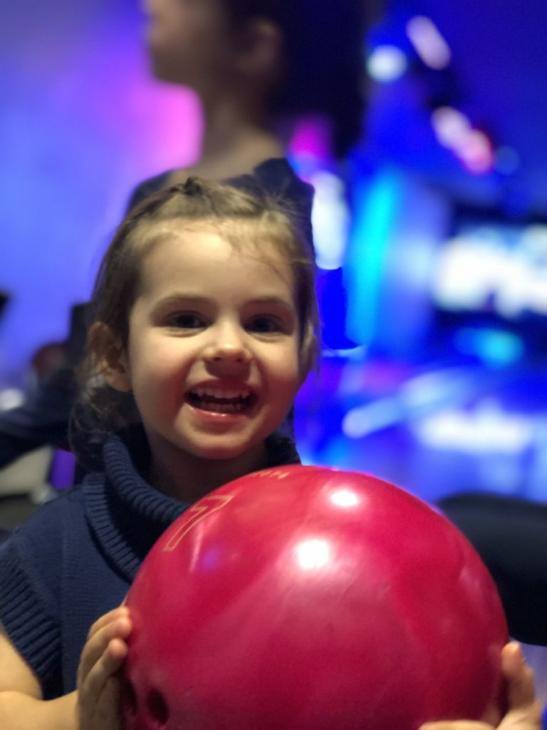 A toddler grins as she holds a bowling ball at Hey Day bowling lanes in Bricktown OKC