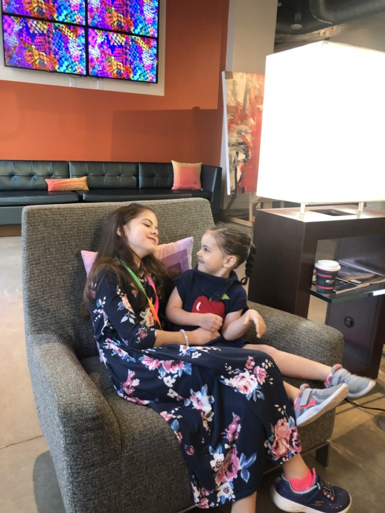 2 girls enjoy each other in the lobby of the Aloft Hotel in Downtown Oklahoma City