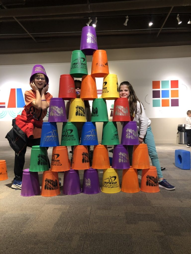 2 kids make pyramid with giant speed stack cups at the Science Museum of Oklahoma in OKC with kids