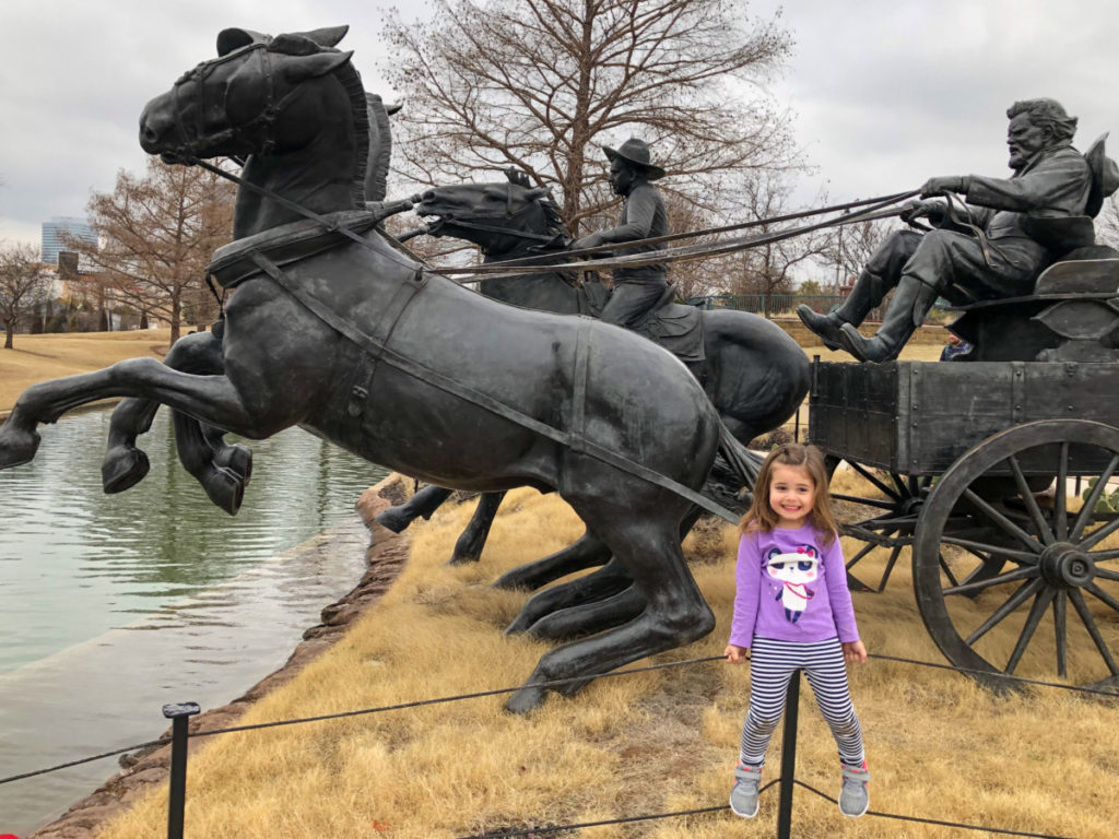 A toddler looks nervous in front of a horse pulling a cart sculture at bricktown river walk in OKC with kids