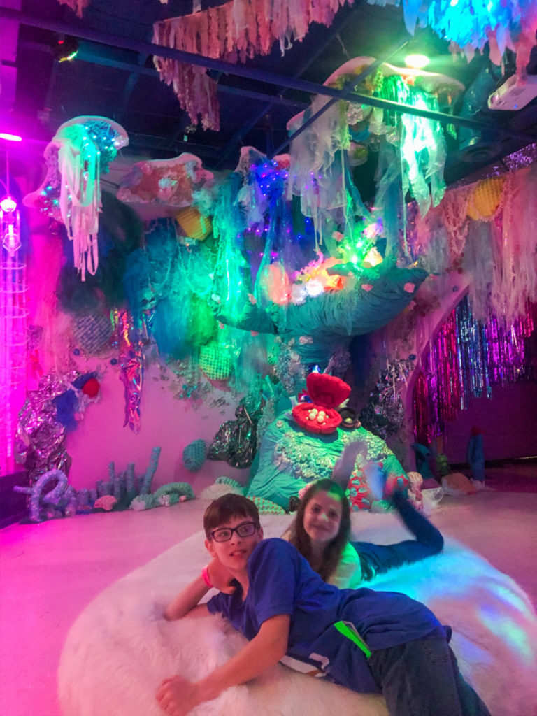 2 kids lay on a fluffy bean bag chair under the city art installation at Factory Obscura in OKC