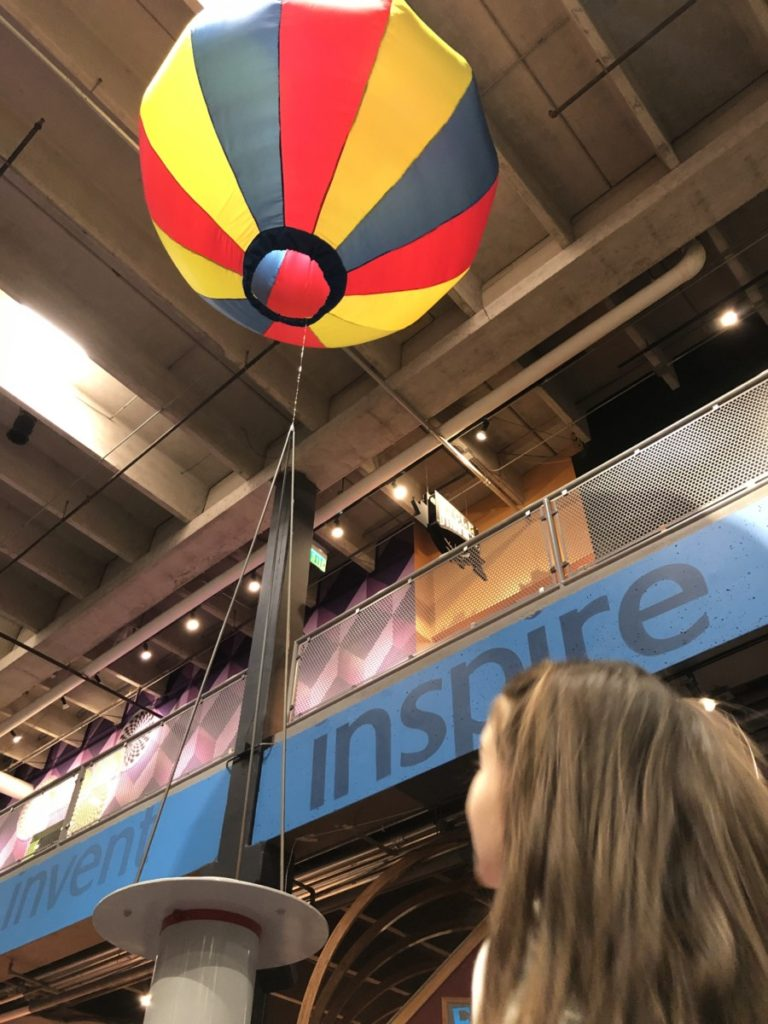 A girl looks up at the 'inspir'e sign and a Hot Air Balloon at Science Museum in OKC with kids