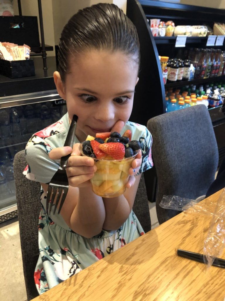 A girl looking cross-eyed at a cup of fruit at Aloft Hotel in Downtown OKC