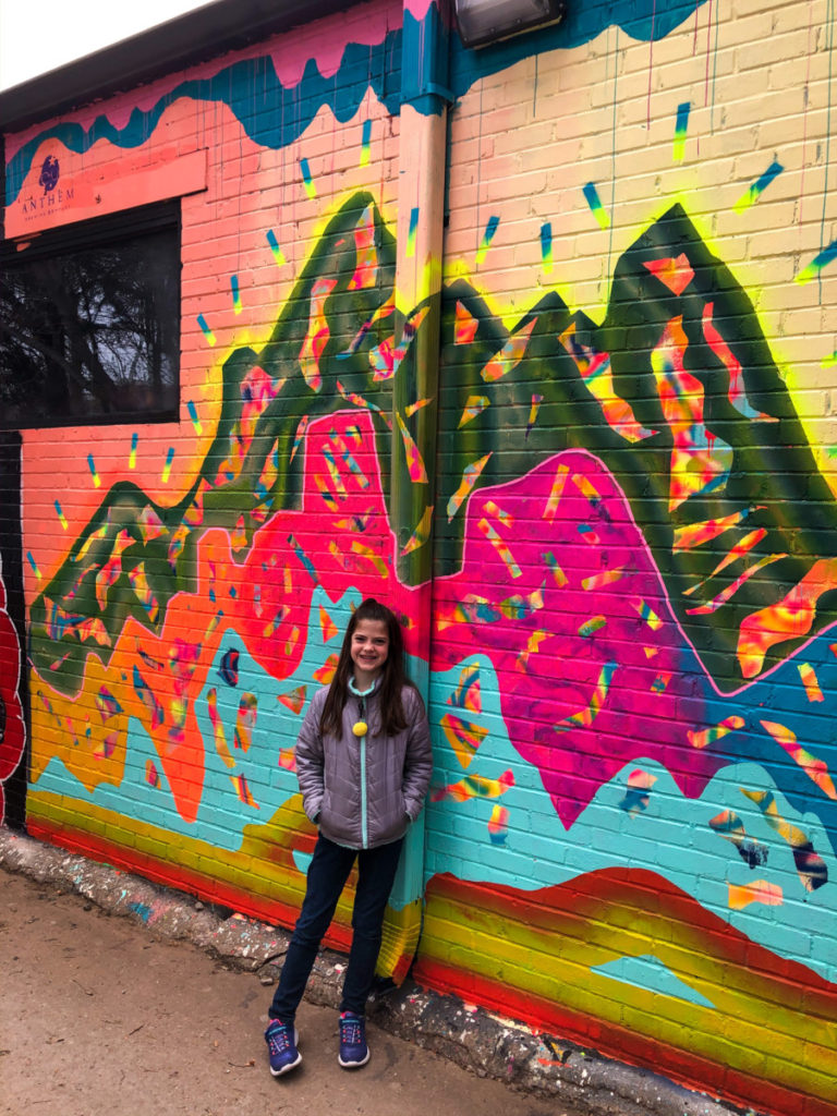 A girl stand in front of brightly colored mountain painting at Plaza Walls in OKC with kids