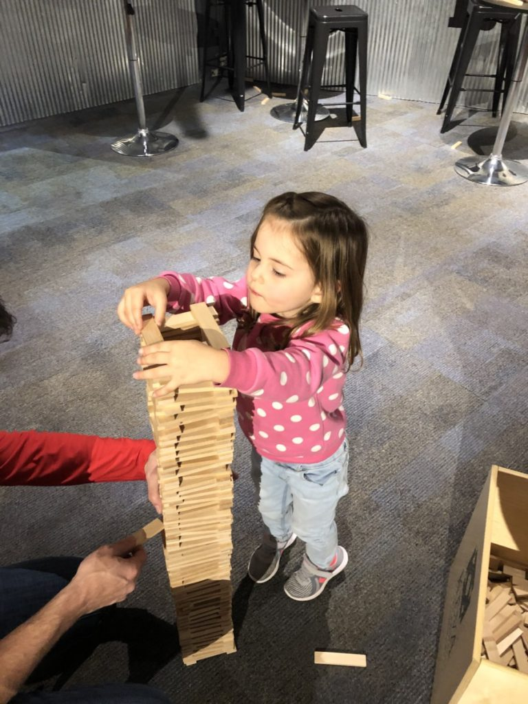 A toddler builds a tower with Keva blocks with her dad at the Science Museum of Oklahoma at OKC with kids