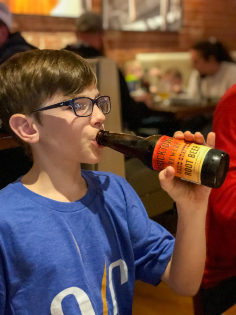 A boy drinks hand crafted Root Beer from a bottler at Bricktown Brewery, OKC with kids