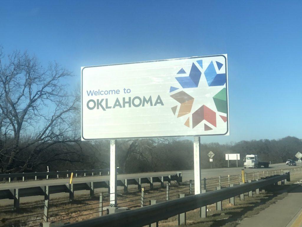 Going to Oklahoma with kids passing the road sign for Oklahoma state