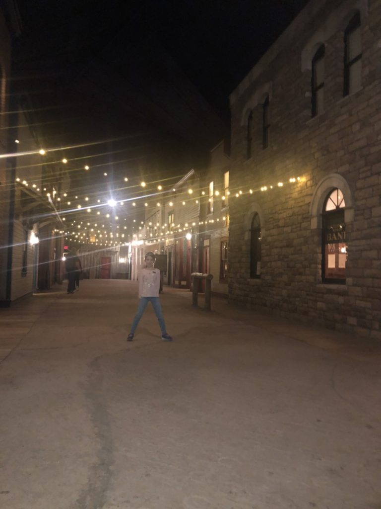 A girl stands under the lights in an Old West Town in the National Cowboy and Western museum in OKC