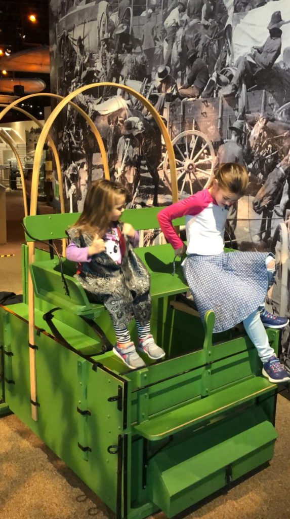 two girls sit on a green covered wagon at the Oklahoma History Center in OKC