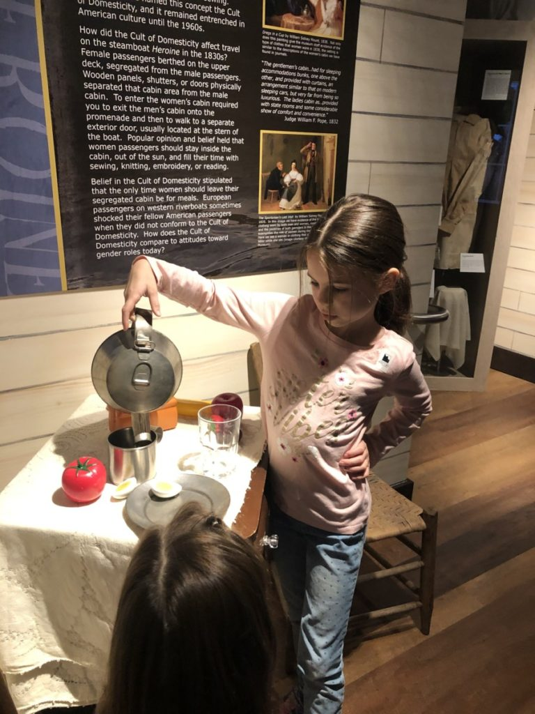 A girl pours into a cup on a steamboat exhibit at the Oklahoma History Center in OKC