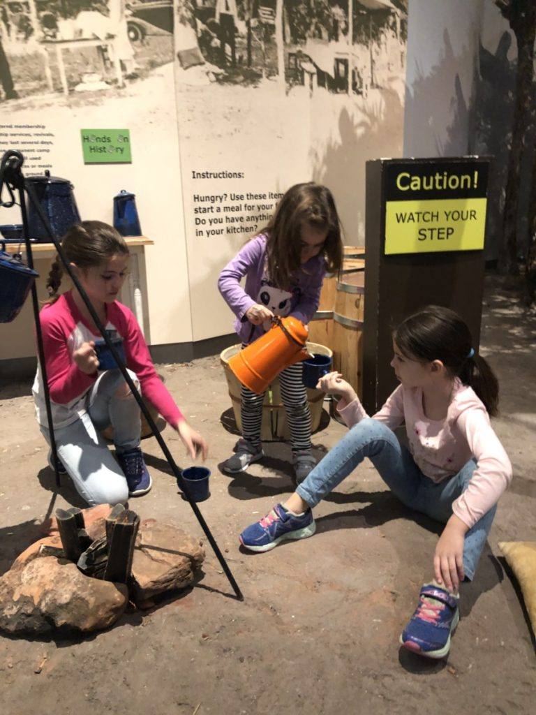 3 girls playing near a fake campfire, pouring from a kettle at the Oklahoma History Center in OKC