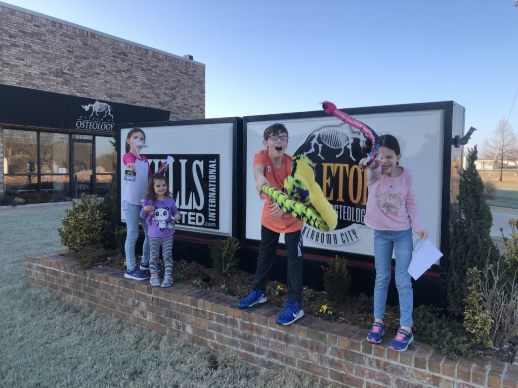 4 kids with stuffed animals from the Osteology Skeleton museum in OKC