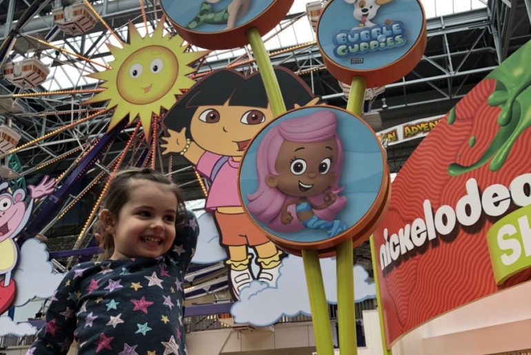 Toddler showing rides El Circulo de Cielo and Guppy Bubbler at Nickelodeon Universe in Mall of America in Minneapolis