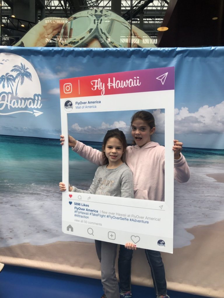 2 girls in an Instagram photo frame at FlyOver Hawaii Ride