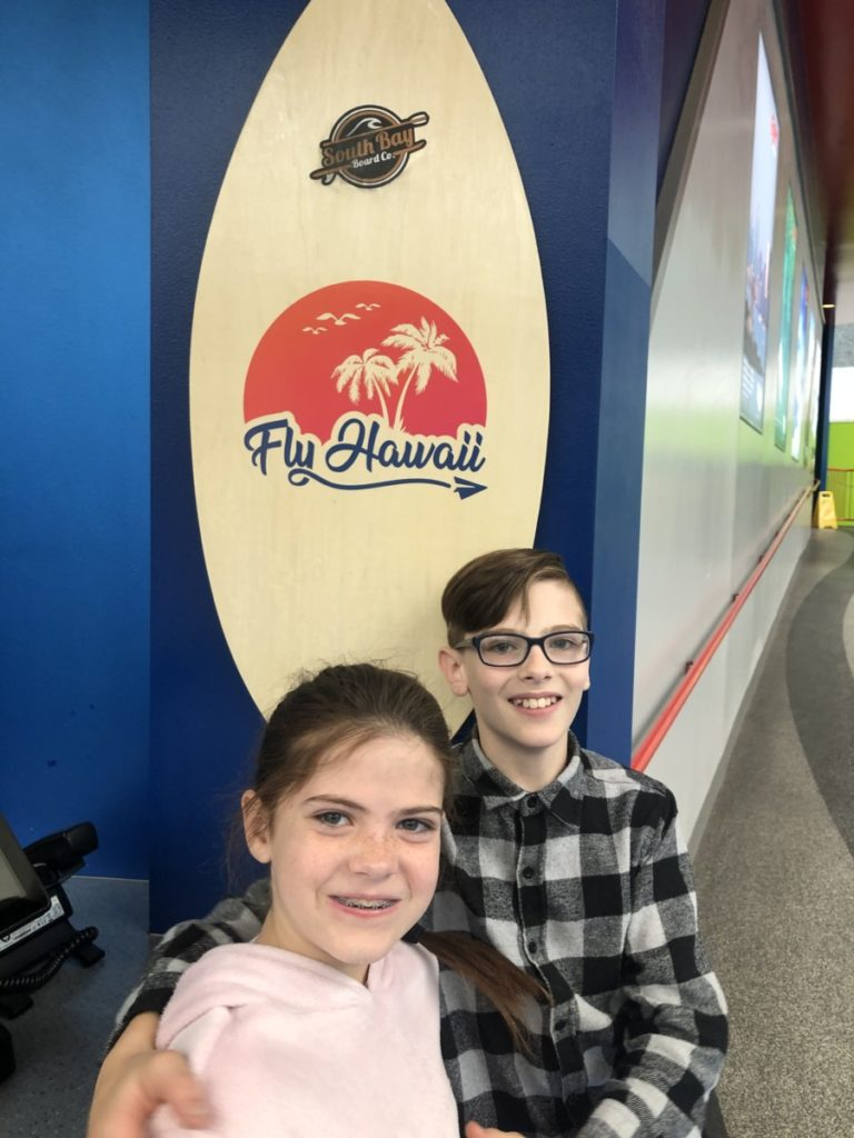 2 kids in front of a surfboard at FlyOver Hawaii in the Mall of America Minneapolis