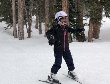 young girl skis in front of trees at Brighton ski Resort