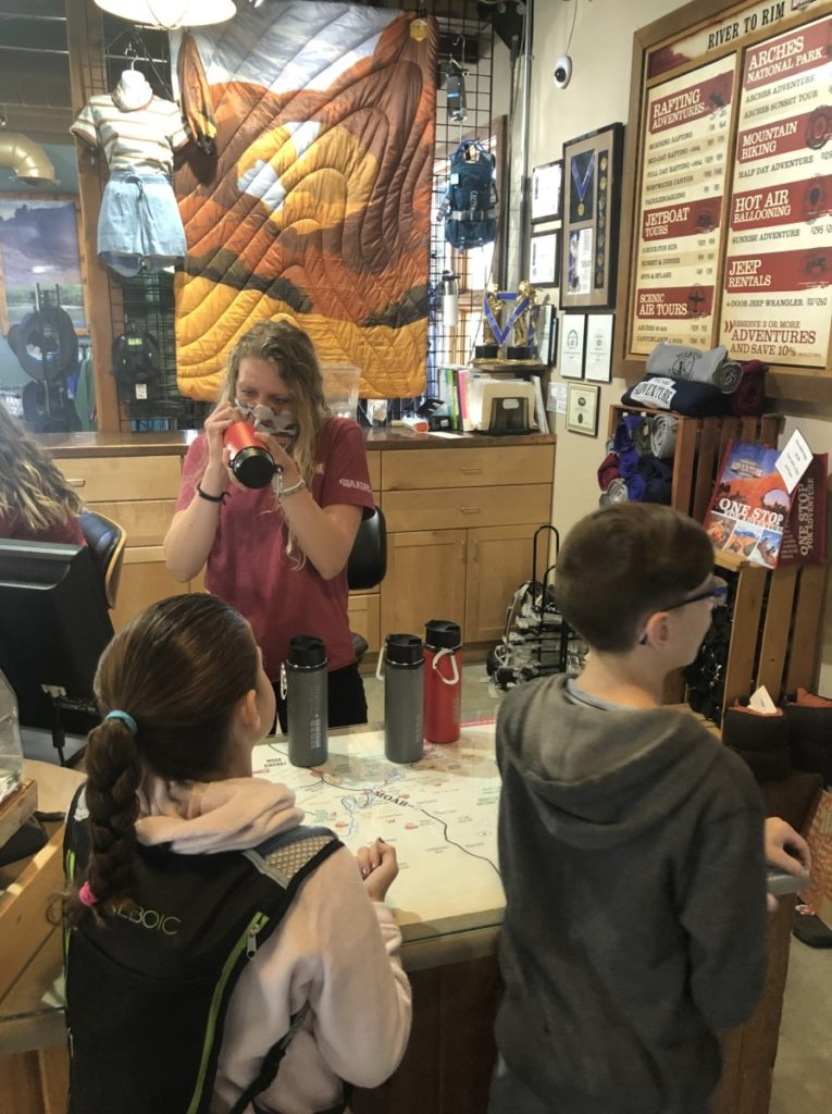 "2 kids receive Hydroflask ""Moab"" water bottles from workers in the Moab Adventure Center before a Hummer tour"