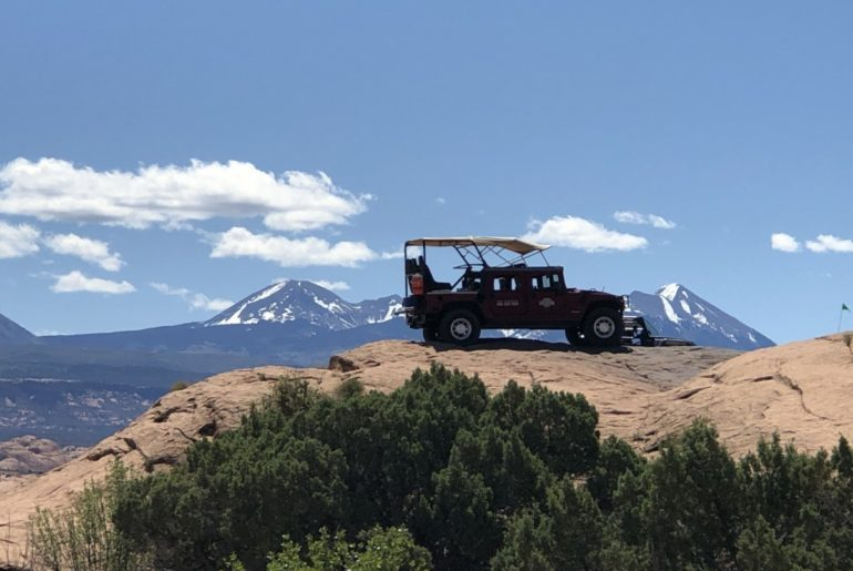 Hummer park on redrock with snowcapped mountains in the distance