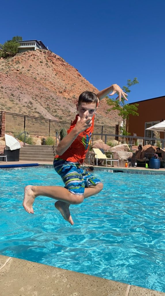 a boy jumps into the pool at Hyatt Place Moab with a red hill in the background