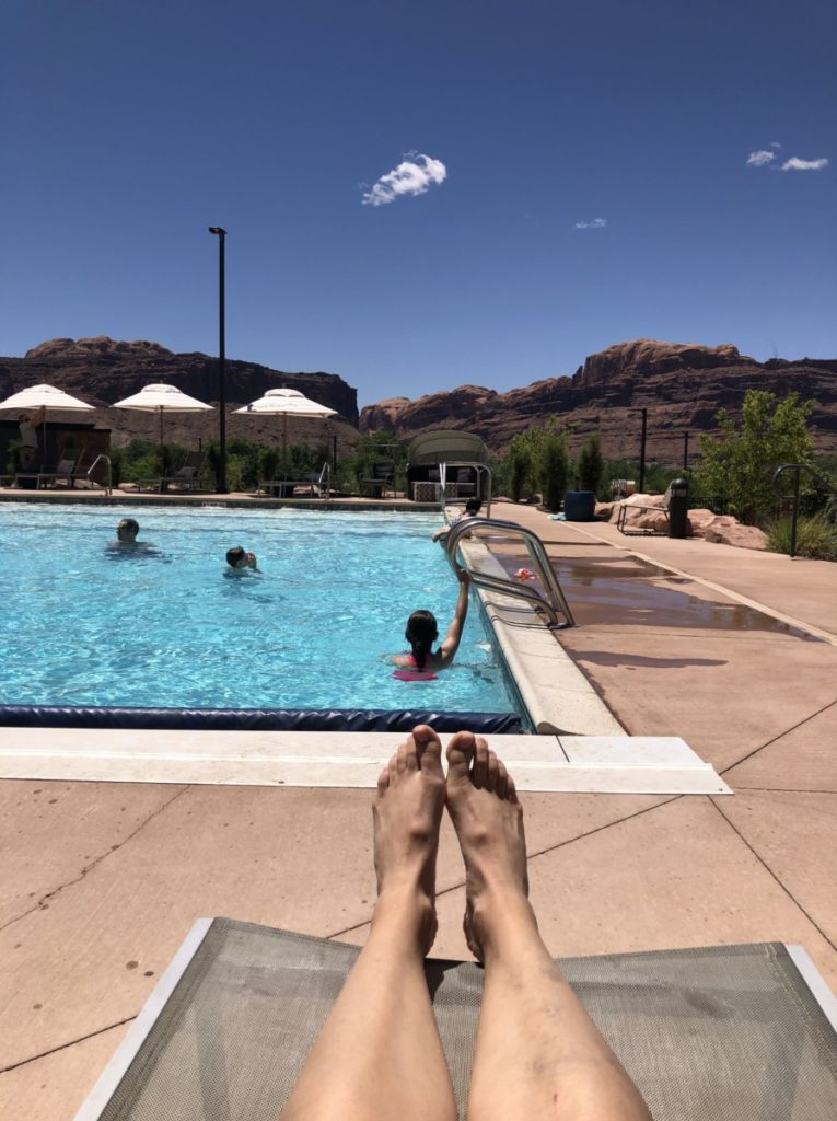 Feet overlooking the pool with kids and red mountains in the background
