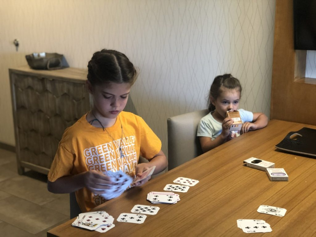 A girl plays cards in Hyatt Place Living room casita in Moab