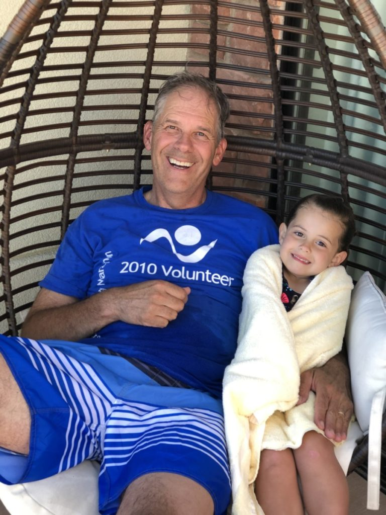 Grandpa and granddaughter sitting in a hanging chair at the casita in Hyatt Place Moab