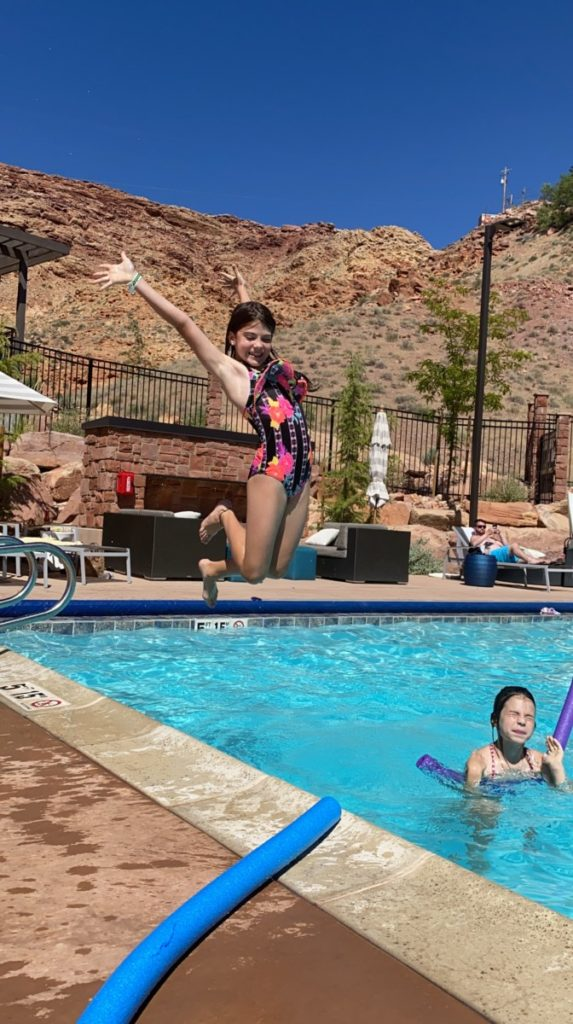a girl jumps for joy at the Hyatt Place in Moab