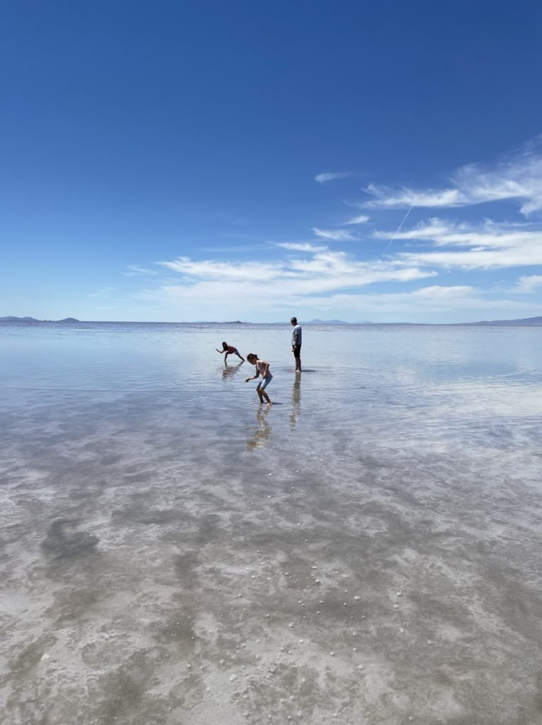 dad and 2 daughters skipping rocks at the Great Salt Lake