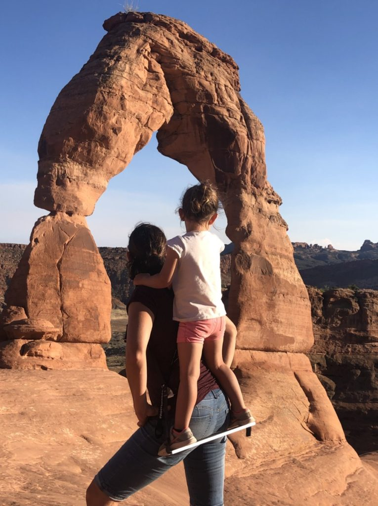 Mom holds daughter on her back in the Piggy back riders at delicate arch in Arches National Park